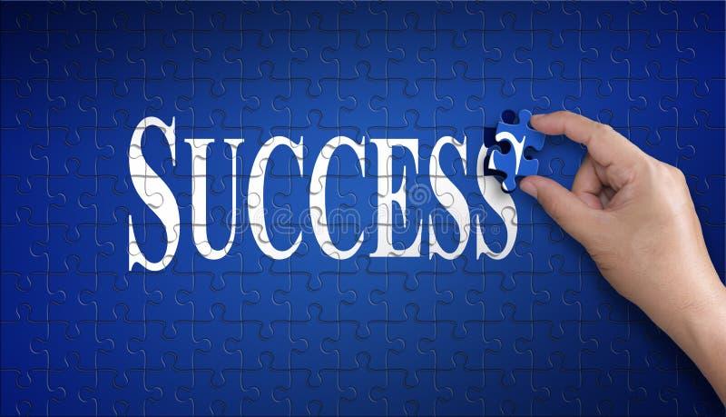 在七巧板的成功词 举行一个蓝色难题的人手 免版税库存图片