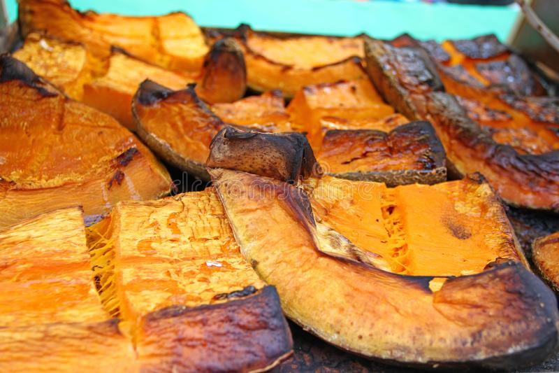 在万圣夜假日烘烤的有机南瓜切片 五颜六色的被烘烤的南瓜背景 南瓜纹理样式 甜点烤pumpki 免版税库存图片