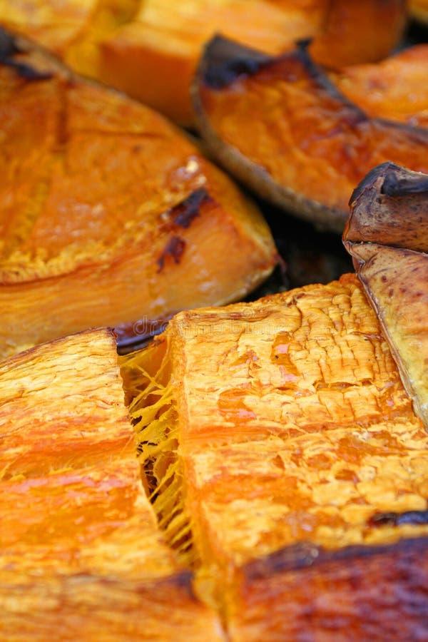 在万圣夜假日烘烤的有机南瓜切片 五颜六色的被烘烤的南瓜背景 南瓜纹理样式 甜点烤pumpki 库存照片