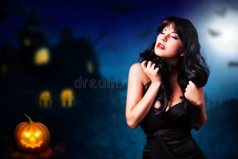 在万圣夜房子前面的可爱的妇女 库存照片