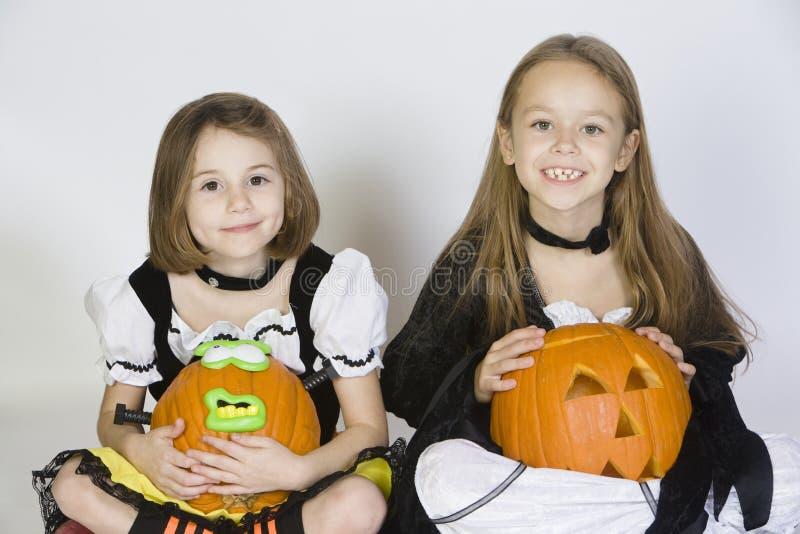在万圣夜服装打扮的两个女孩拿着杰克O灯笼 库存照片