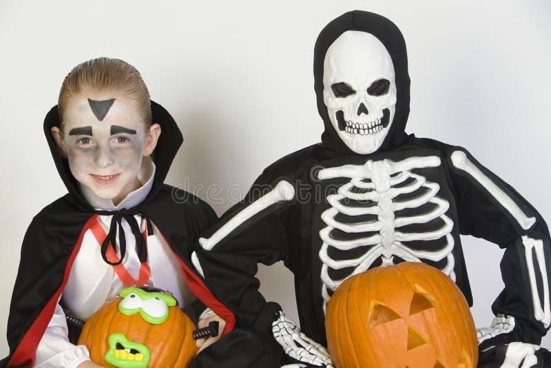 在万圣夜服装打扮的两个男孩拿着杰克O灯笼 免版税库存图片