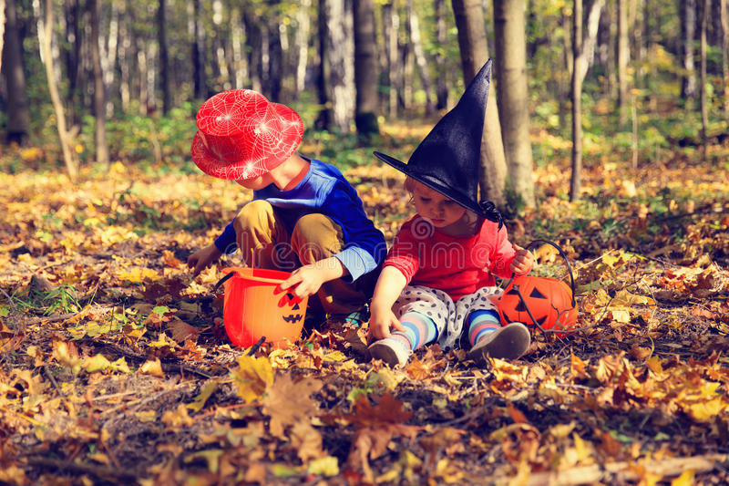 在万圣夜服装的孩子使用在秋天公园,把戏或款待 图库摄影