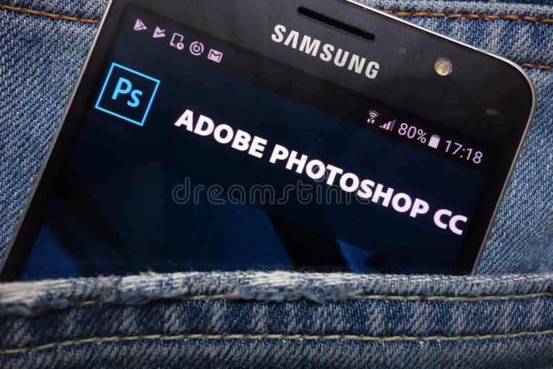 在三星智能手机显示的Adobe Photoshop网站掩藏在牛仔裤装在口袋里 免版税库存照片