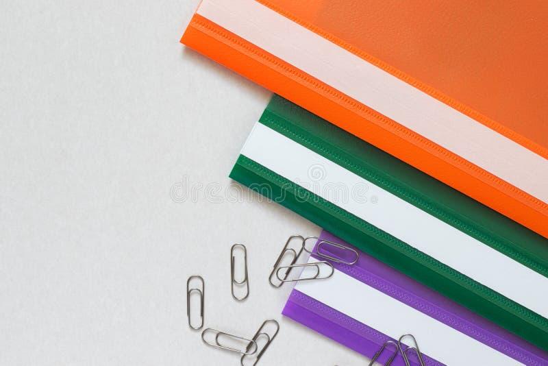 在三种颜色的塑料文件夹与夹子 免版税库存照片