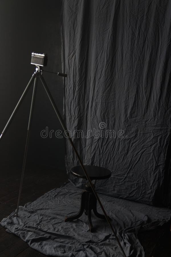 在三脚架的老照相机在屋子里站立 库存图片