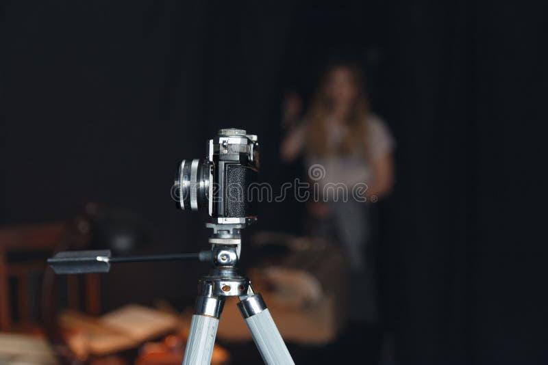 在三脚架的老照相机在屋子里站立 库存照片
