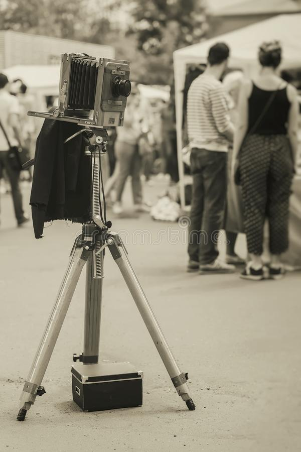 在三脚架的葡萄酒照片木照相机以走的人为背景在公园 处理与减速火箭的乌贼属样式 免版税图库摄影