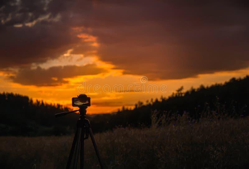 在三脚架clouse日落记录时间流逝的手机  捷克风景 免版税图库摄影