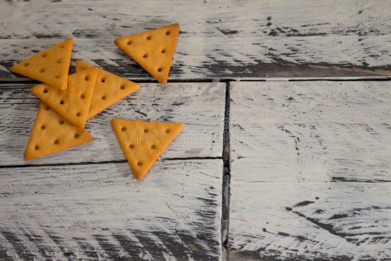 在三角形状的咸曲奇饼在一个白和黑人土气委员会 免版税图库摄影