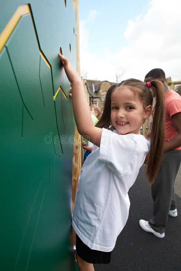 在上升的墙壁上的女孩在学校体育类 免版税库存照片