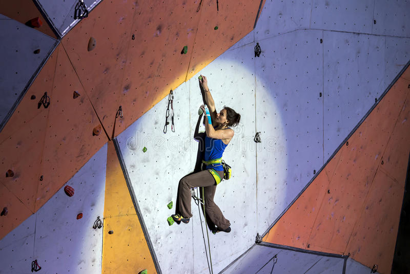 在上升的墙壁上的女性体育登山人 免版税库存图片