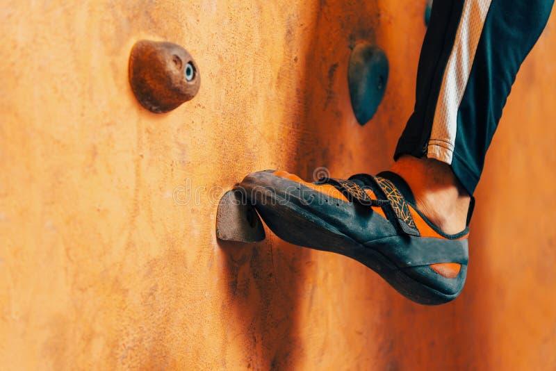在上升的墙壁上的男性脚 免版税库存图片