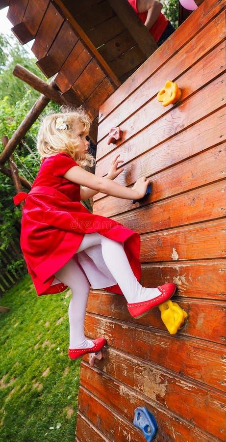 在上升的墙壁上的白肤金发的小女孩 免版税库存图片