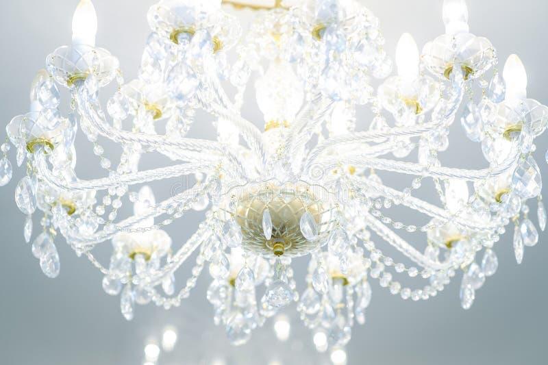 在上升限度的豪华水晶枝形吊灯与被点燃的灯 免版税库存图片