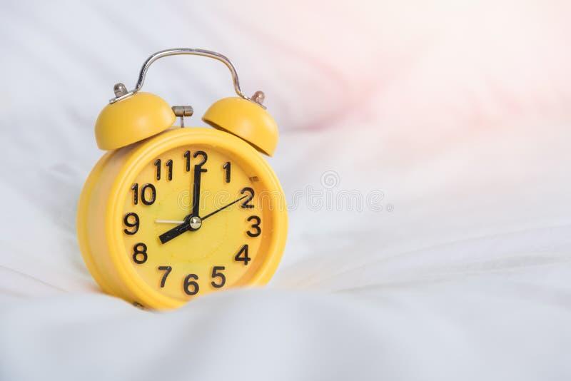 在上午8点的黄色闹钟在床上 图库摄影