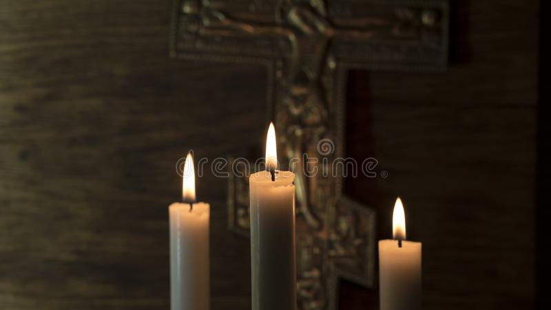 在上帝的信念 以三个蜡烛为背景的在十字架上钉死 库存图片