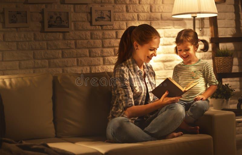 在上床的母亲前的家庭读给她的儿童女儿bo 免版税图库摄影