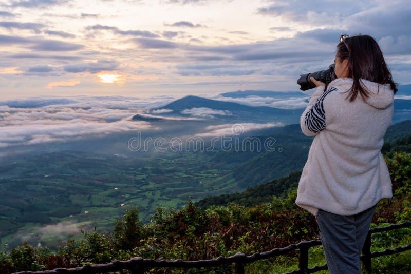 在上流的日出期间妇女游人在冬天使用一个DSLR照相机拍摄的自然风景太阳雾山 免版税库存图片