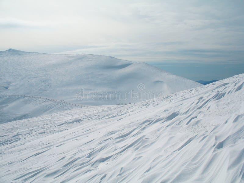 在上流的白色积雪的山峰 背景寒冷冬天 免版税库存照片