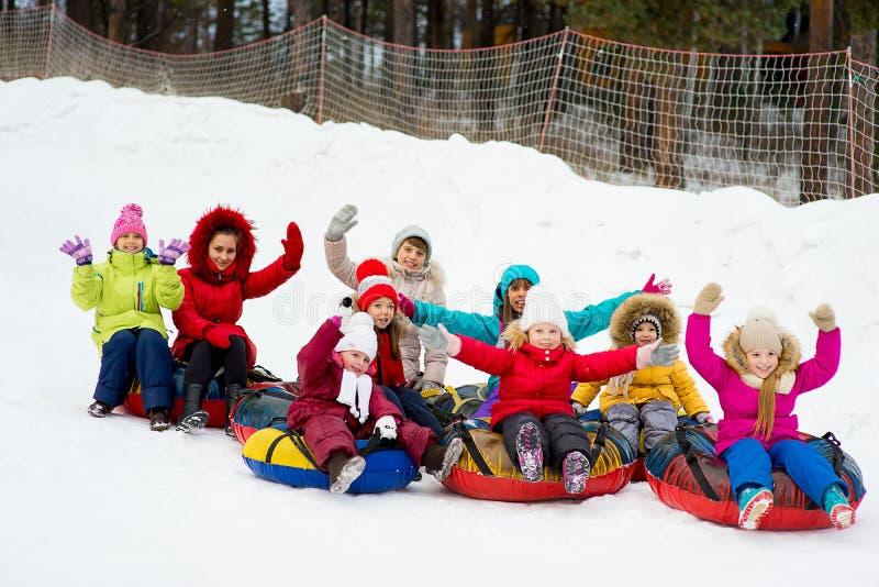 在下坡雪管的孩子冬日 免版税库存图片