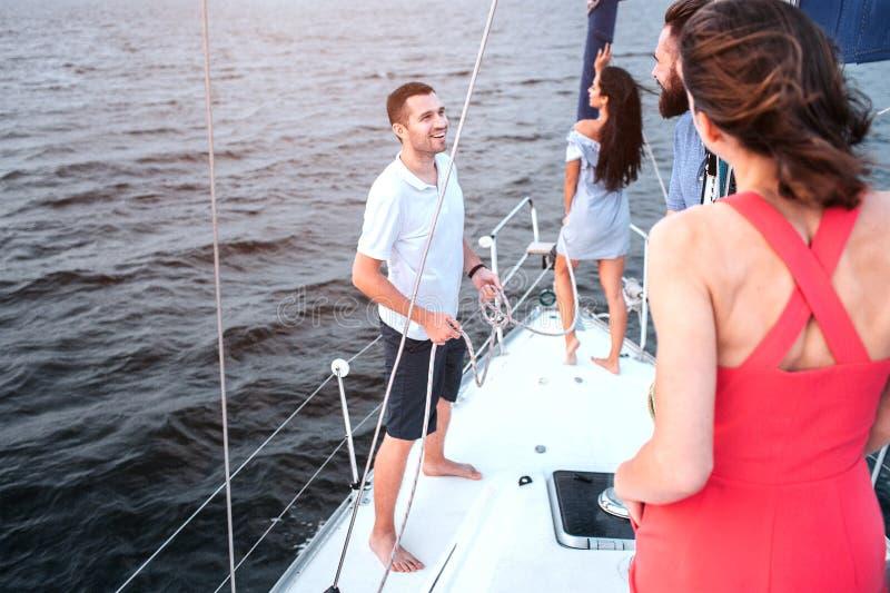 在下来游艇和神色弓的深色的立场  她摆在 两年轻人看和谈话互相 Readhead 库存照片