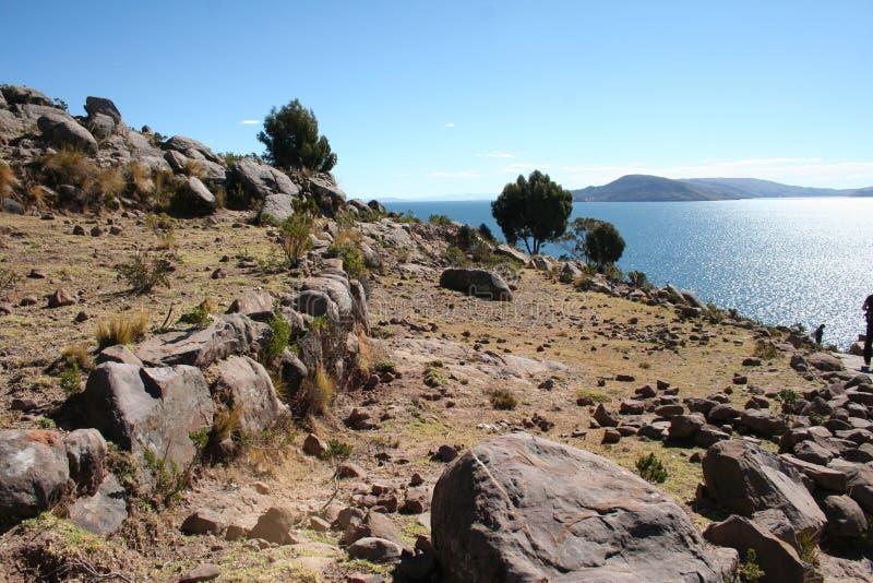 在下来Titicaca湖的毗邻的领域中的石道路在晴天 免版税库存图片