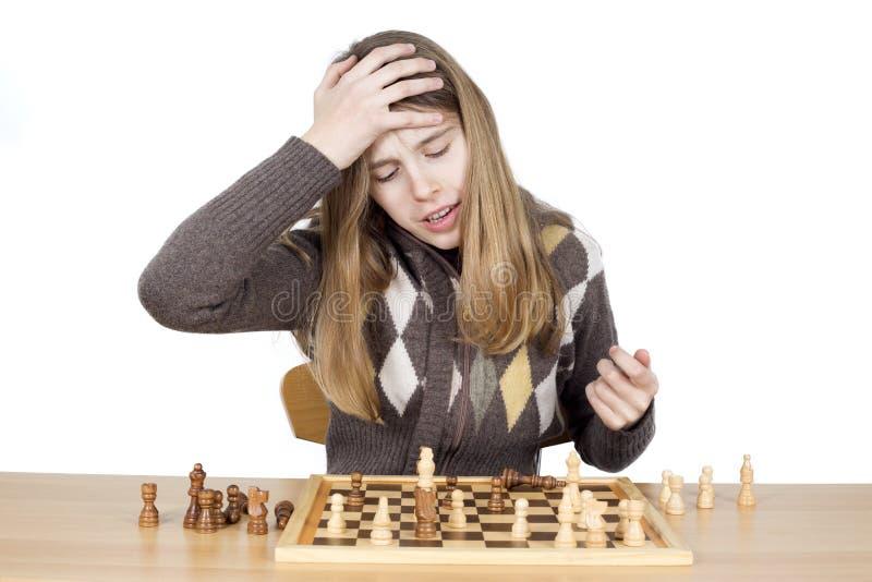 在下棋比赛期间,掴在头的年轻人非常失望的女孩手说哈,表示差错的遗憾她做了 免版税库存照片