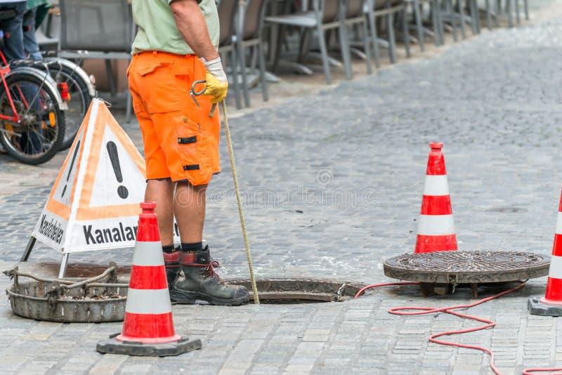 在下水道渠道的街道工作与警告签到渠道工作的德国词 免版税图库摄影