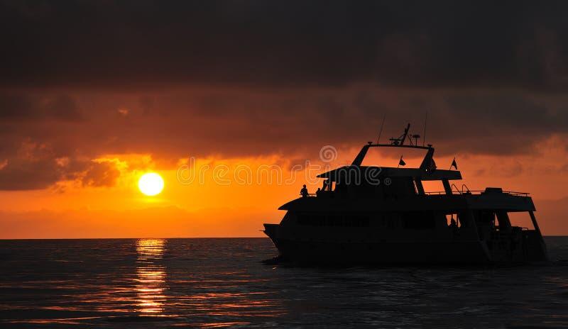 在下潜小船的日落   免版税库存图片