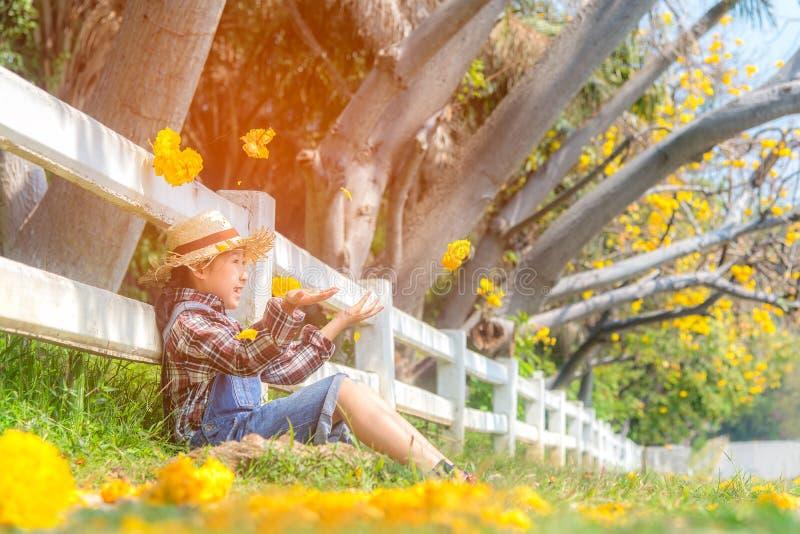 在下落的叶子的亚洲微笑的孩子女孩开会和投掷黄色花秋天在公园, 免版税库存图片