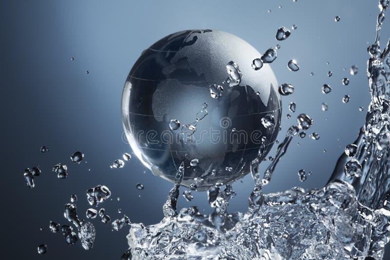 在下落水飞溅的玻璃地球行星在蓝色 库存照片