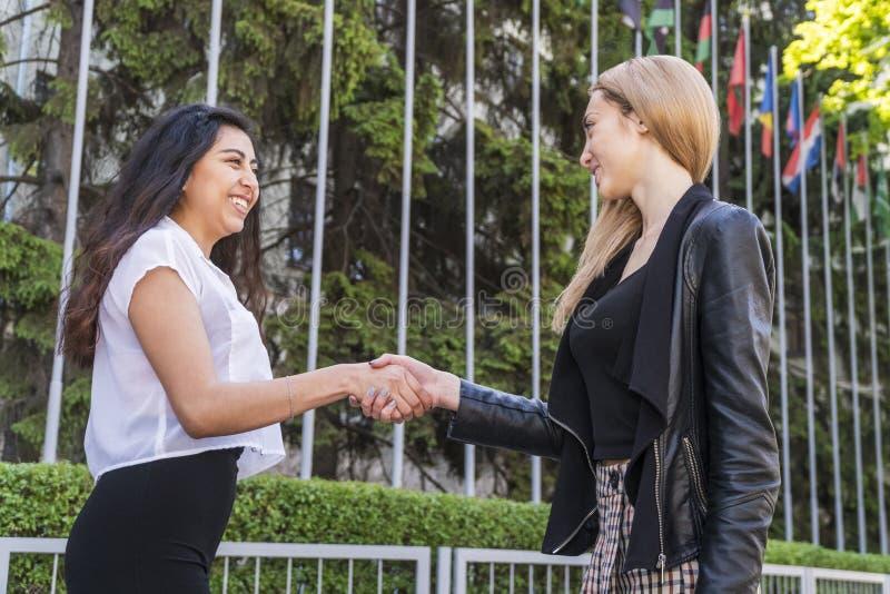 在不同的国籍的两名妇女的之间握手 免版税库存图片