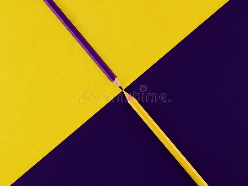 在不同的背景的紫色和黄色铅笔 免版税库存照片