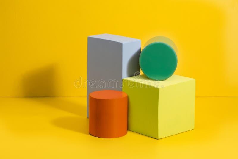 在不同颜色的几何形状在黄色背景 免版税库存图片