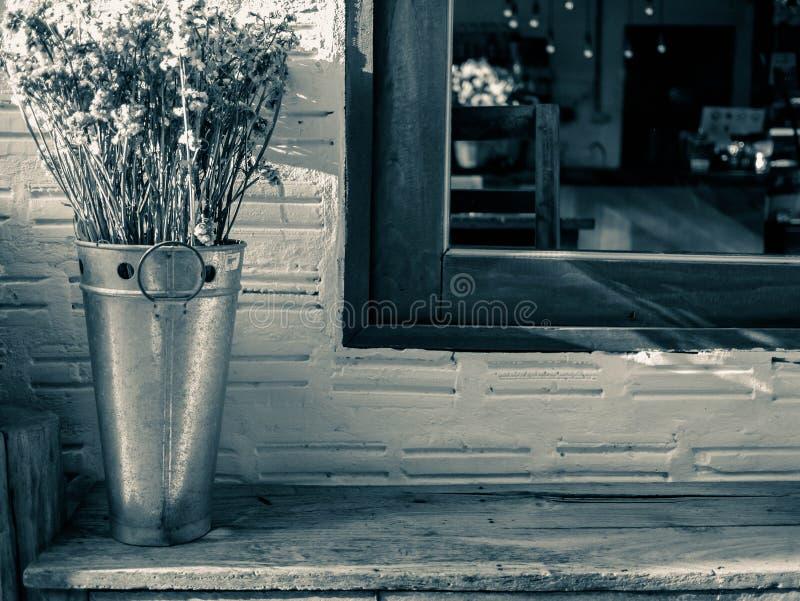 在不锈钢坦克的干花在临近与阳光的木椅子窗口在晚上 背景概念 库存图片