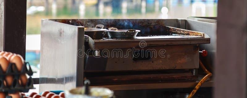在不锈钢平底锅的新鲜的抽烟的食物在高温废气刺激的火炉,准备为油煎早餐膳食食物在室内厨房里 库存图片