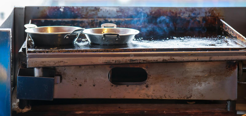 在不锈钢平底锅的新鲜的抽烟的食物在高温废气刺激的火炉,准备为油煎早餐膳食食物在室内厨房里 免版税库存图片