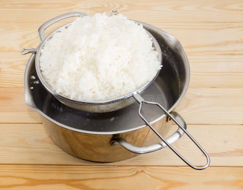 在不锈钢筛子的煮沸的白米在储蓄罐 免版税库存图片