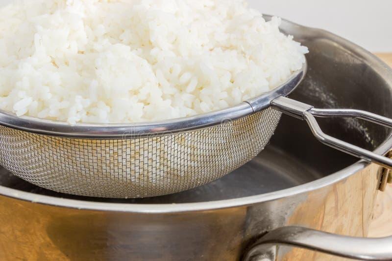 在不锈钢筛子的煮沸的米在罐特写镜头 库存照片