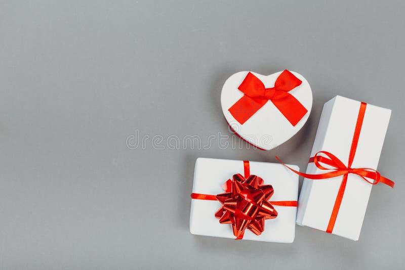在与一条红色丝带的纸和灰色表面上的一把弓包裹的美丽的礼物盒 库存照片