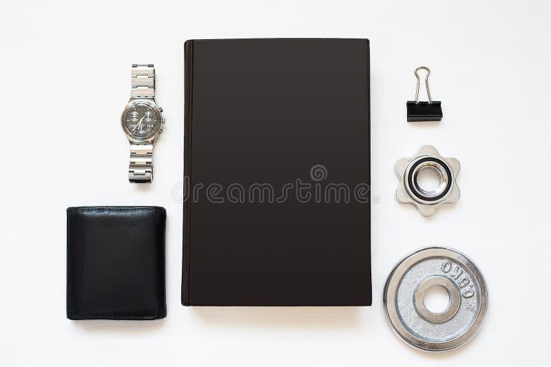 在与人` s事的白色织地不很细木背景隔绝的空白的黑笔记本 平的位置书 顶视图 复制空间 库存照片