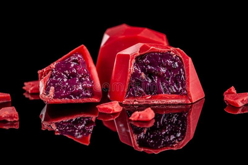 在与反射的黑背景隔绝的巧克力红色糖果心脏 情人节浪漫点心构成 免版税库存图片