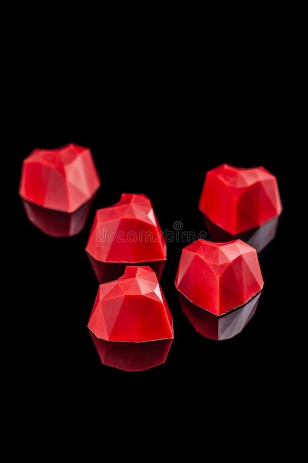 在与反射的黑背景隔绝的巧克力红色糖果心脏 情人节浪漫点心构成 图库摄影