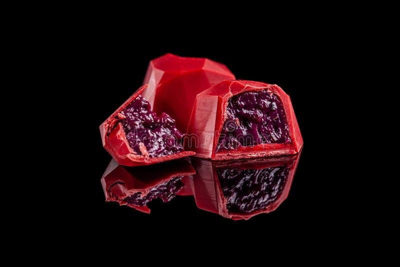 在与反射的黑背景隔绝的巧克力红色糖果心脏 情人节浪漫点心构成 免版税图库摄影