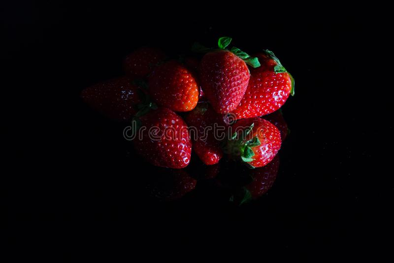 在与反射的黑背景隔绝的新鲜的草莓 库存照片