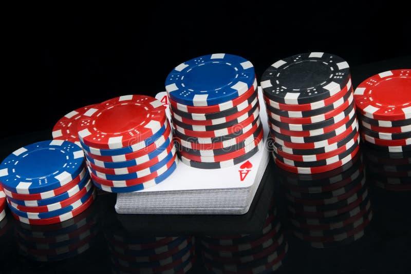 在与反射的黑背景,在卡片组,有色的芯片金字塔打的扑克 免版税图库摄影