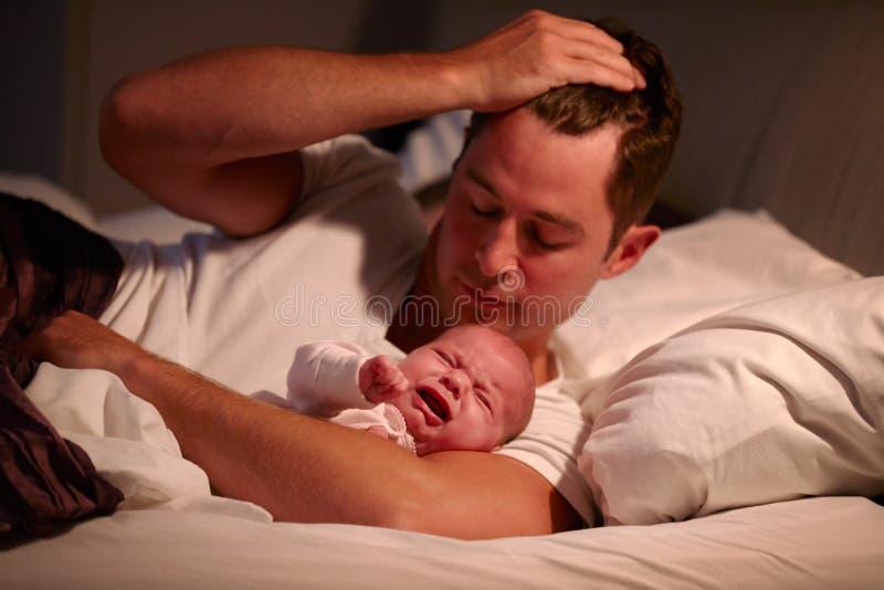 在与哭泣的小女儿的床上的父亲 免版税库存图片