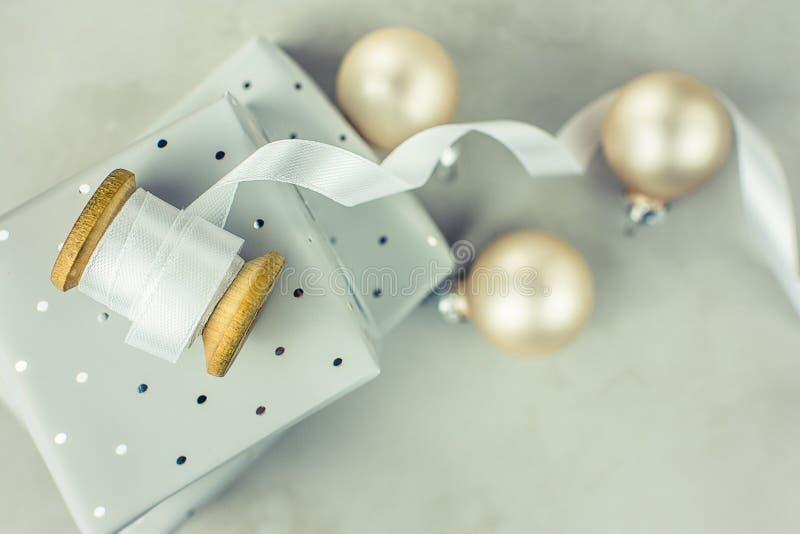 在与圆点样式的锡箔包裹的被堆积的礼物盒 有白色的木短管轴卷曲了丝绸丝带,圣诞节中看不中用的物品 免版税库存照片