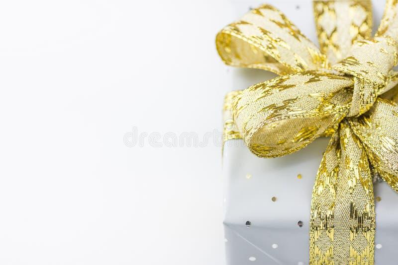 在与圆点金黄丝带的灰色锡箔包裹的典雅的礼物盒 圣诞节新年华伦泰提出购物销售 库存照片